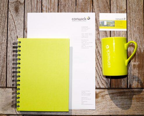 Briefpapier der Firma Conwick liegt mit einer Tasse und einer Visitenkarte auf einem Holztisch