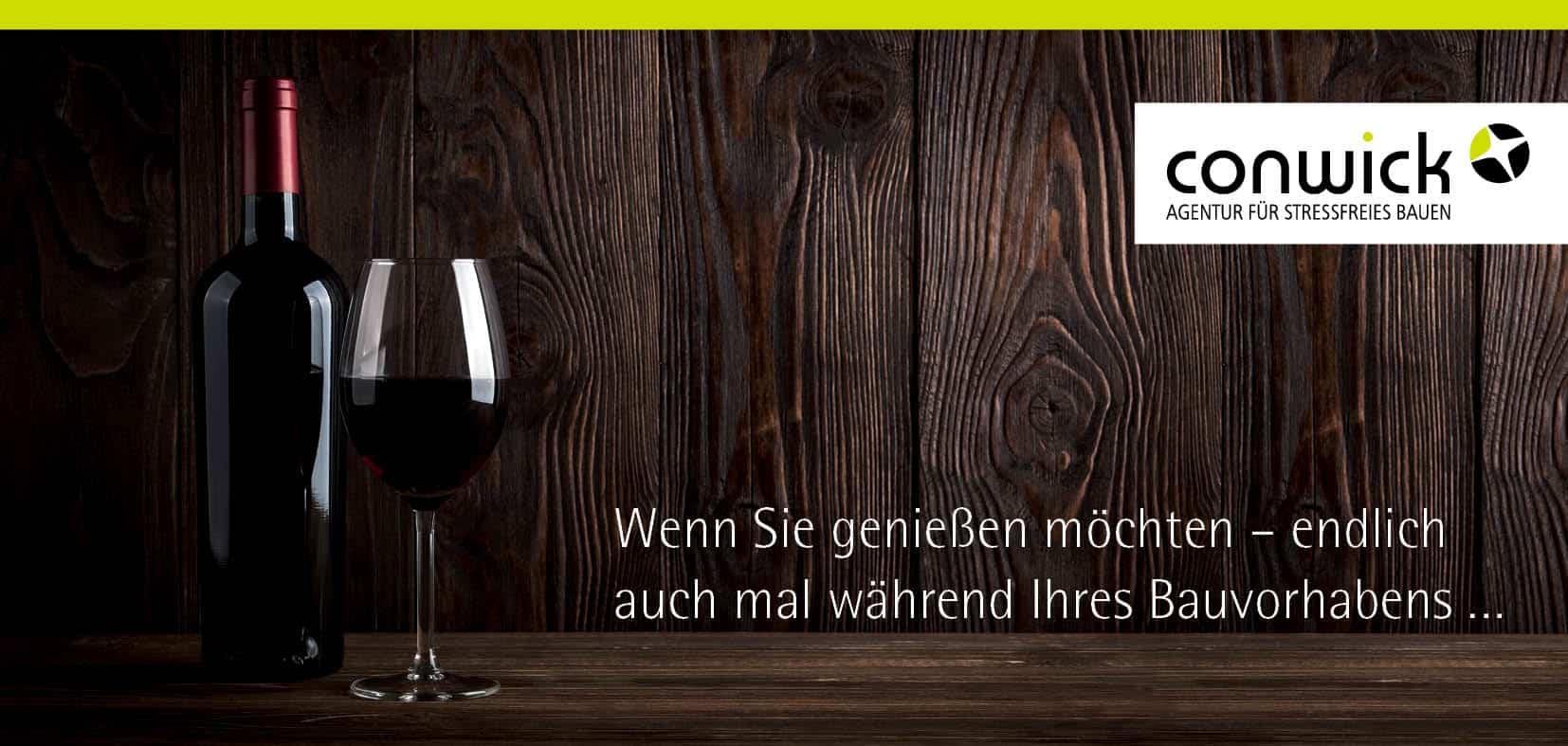 Ein Glas Rotwein und eine Flasche stehen vor einer Holzwand